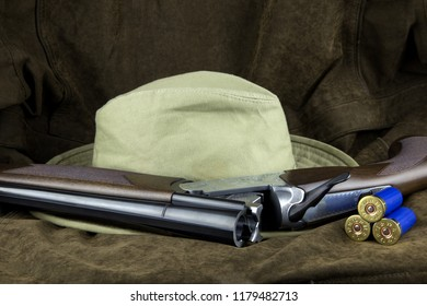 Shotgun and hat with cartridges on an outdoor coat