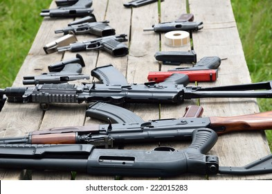 A shotgun, pistols and other firearm are laid out on the table outdoors.