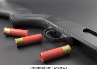 A shotgun and red shotgun shells