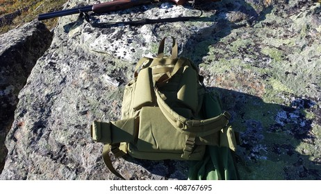 shotgun resting on big boulder on mountain with green backpack with green hunting net with grouse birds