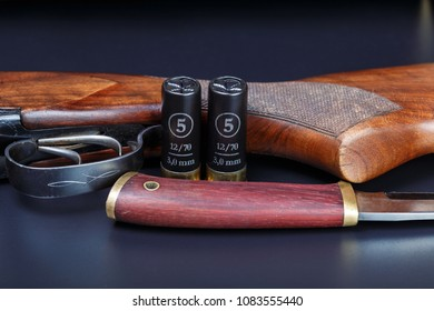 Shotgun, shotgun shells and hunting knife on a black background