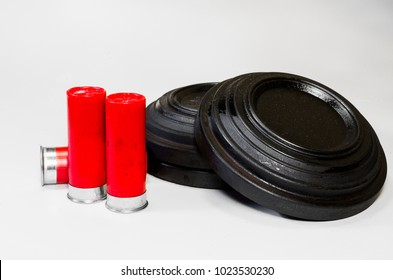 Shotgun shells and a stack of clay pigeons, aka skeet.