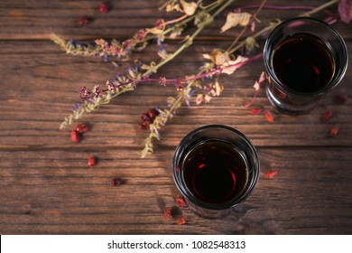 Shots of alcoholic drink on dark rustic wooden background. Herbal bitter liqueur with different natural ingredients, above