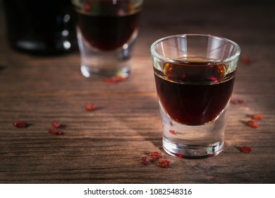 Shots of alcoholic drink on dark wooden background. Herbal bitter liqueur with different natural ingredients.
