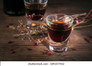 Shots of alcoholic drink on dark wooden background. Herbal bitter liquor with different natural ingredients.
