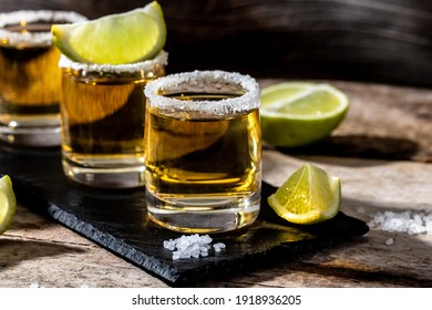 shots of gold Mexican tequila with lime and salt. Alcoholic Mexican national drink.