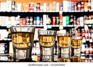 Shots of whiskey lined up on bar in front of a variety of bottles.