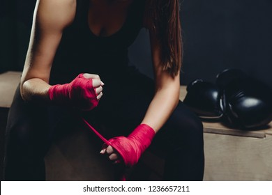 Shoulder girl in uniform on black background is preparing for tough fight, wraps her sports protective bandages of red and pink color strong fist, Boxing gloves near
