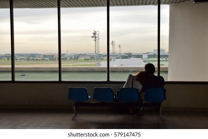 Shoulder lean,Silhouette of couple are sitting on seats beside the glass window with morning sky  at  airport with aircraft background, Don Muaeng airport, Thailand