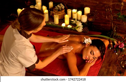 Shoulder and neck woman oil pressure massage by master acupressure therapy professiona with top view large group of candles in day spa.
