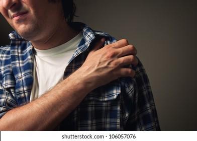 Shoulder pain. Adult man holding his painful shoulder.