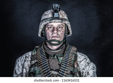 Shoulder portrait of experienced army soldier, military conflict veteran, skilled marine fighter in ragged camouflage uniform, advanced helmet and ammo belts on chest, studio shot on black background