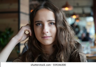 Shoulder portrait of young girl in brown blouse. She touching her long hair by fingers. Long haired woman sitting in coffe shop. Dark-brown eyes, mouth closed