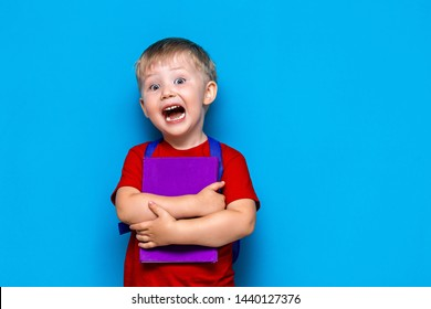 shouting boy with book and schoolbag, upset surprised and afraid of school. back to school. on blue background.