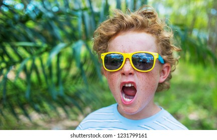 shouting boy - emotional portrait of caucasian teen boy, the boy shouts loudly with his mouth wide open against the background of greenery