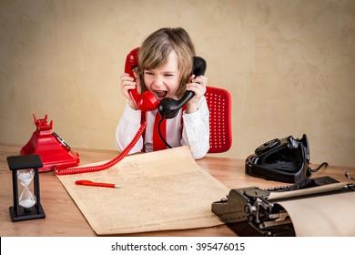 Shouting child businessman with retro phone. Success communication business concept