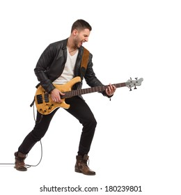 Shouting guitarist in black leather jacket plays the bass guitar. Full length studio shot isolated on white.