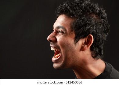 A shouting man in a dark background