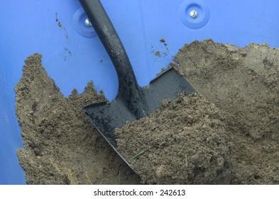 shovel in a blue wheel barrow with dirt