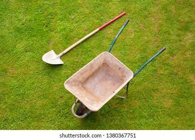 Shovel and empty barrow on freshly cut garden grass.
