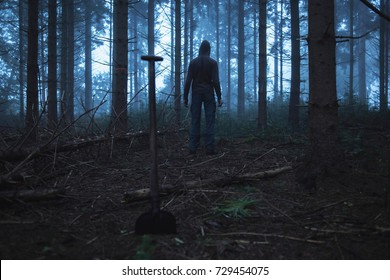 Shovel and man in hoody in spooky misty pine forest.