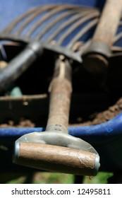 Shovel, pick and rack in a blue wheelbarrow