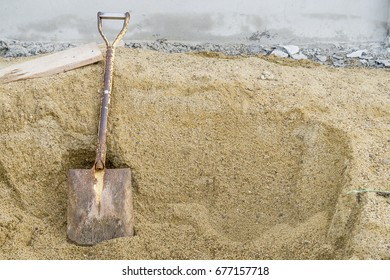 Shovel placed on a pile of sand for construction work.