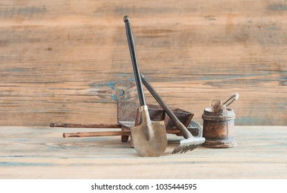 shovel, rake and bucket on wooden table and wall background
