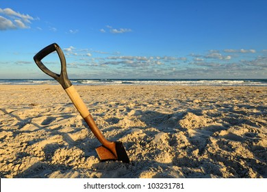 Shovel in Sand at the Beach. Wide angle image of a rusty shovel in the sand on a beach under a partly cloudy blue sky.