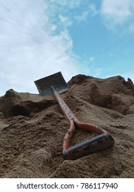 Shovel with sand pile at home construction site. The sky and the clouds are the background.