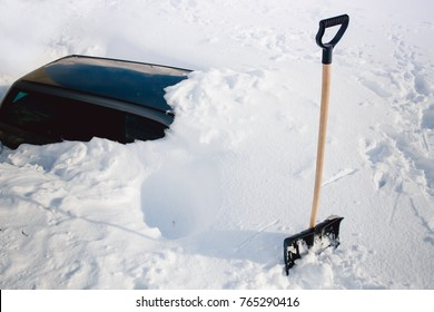 Shovel in snow, in background the car is covered. Winter, abnormal snowfall.