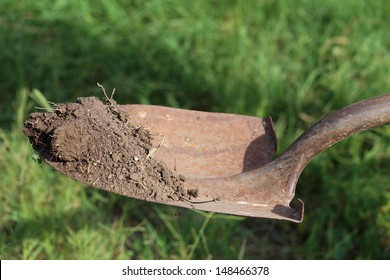 A shovel, or spade, holding up dirt above the ground