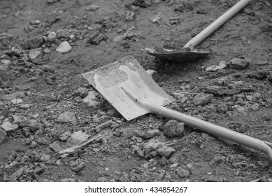Shovel stuck in a pile of dirt,Construction worker is trying to move a kurb,Black and White tone