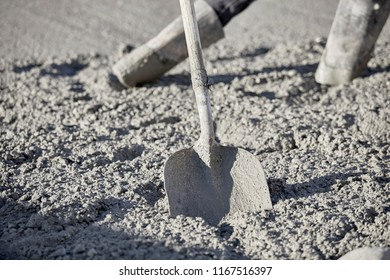 A shovel in wet cement with the boots of a mason behind it and shallow depth of field