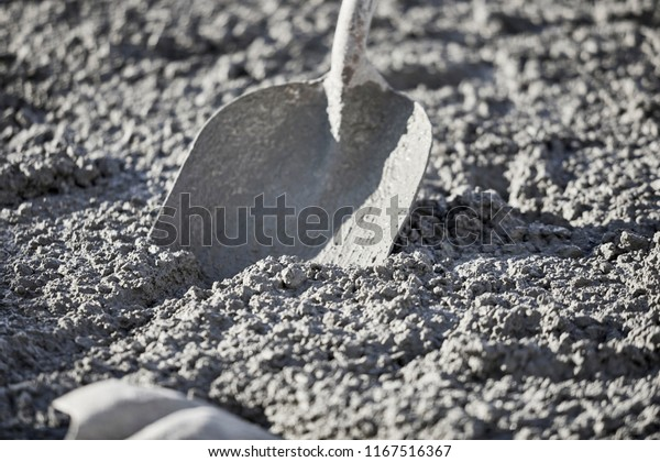 A shovel in wet cement with shallow depth of field