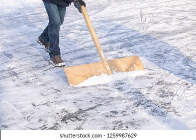 Shoveling snow with wooden shovel from ice for speed ice skating with wooden shovel