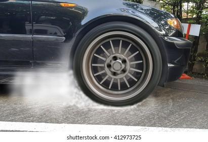 Show burning tires racing car in racetracks.