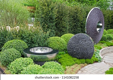 SHOW GARDEN WITH TOPIARY AND MODERN PEBBLE DECORATIVE CRATIONS . CHELSEA. LONDON. MAY 2012. A stylish modern urban garden topiary buxus bushes and creative decorative features  with stainless steel