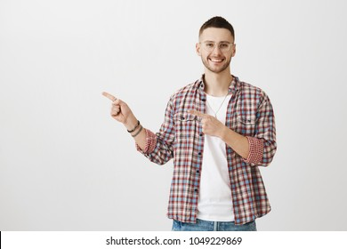 Show me what you have there. Studio portrait of amazing good-looking guy in glasses pointing left with both index fingers, smiling broadly at camera over gray background. Man searching head office