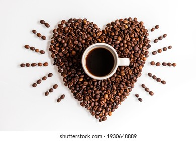 Show your love with a coffee. A cup inside a beating heart made of coffee beans on a white background.