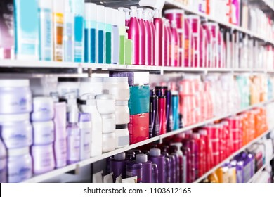 showcase with bottles of shampoos and conditioners in the hair care store.
