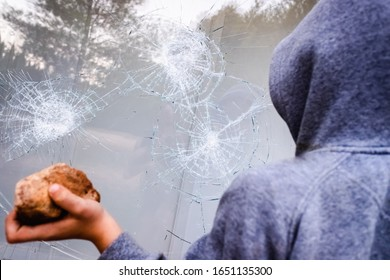 Showcase with broken glass during a protest in a city with protesters.