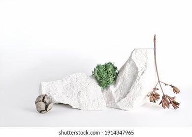 Schaufenster für natürliche Ökoprodukte. Steine, trockener Buszweig, Moos auf weißem Hintergrund. Muster für sauberes, umweltfreundliches Kosmetikprodukt. moderne Stillleben erschossen.