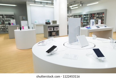 Showcase with smartphones in a light electronics store. Technology store with light modern interior.
