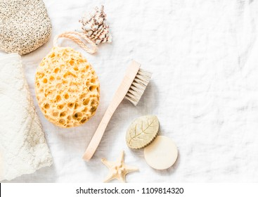 Shower accessories - face brush, sponge, pumice stone, towel, soap on a light background, top view. Cleansing of the skin health concept. Flat lay