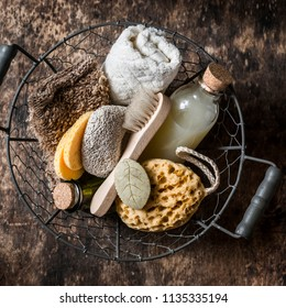 Shower accessories in vintage basket - shampoo, sponge, soap, facial brush, towel, washcloth, pumice stone. On wooden background, top view