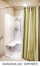A shower designed for disabled or handicapped roll-in access, with grab bars, adjustable, handheld shower head, and a seat to sit on.