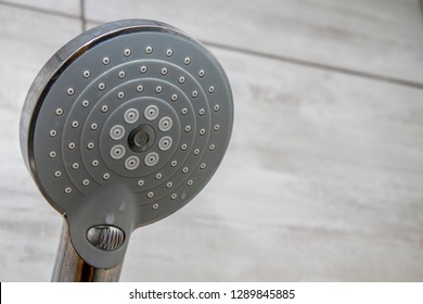 Shower head fitting attached to a tiled bathroom wall.