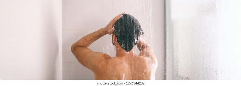 Shower man washing hair rinsing shampoo in bathroom banner panorama. Showering person at home lifestyle. Young guy taking a shower.