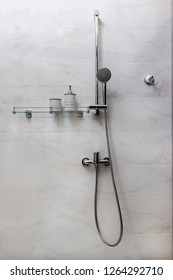 Shower set ion a marble wall with a glass shelf and accessories